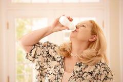 妇女饮用的酸奶在厨房里 库存照片