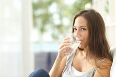妇女饮用水在家和看您 免版税库存图片