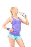 妇女饮用水在跑步以后 免版税图库摄影