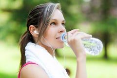 妇女饮用水在跑以后 图库摄影