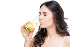 妇女饮用水用在白色隔绝的柠檬 库存图片