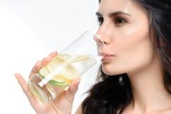 妇女饮用水用在白色隔绝的柠檬 图库摄影
