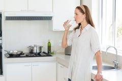 妇女饮用水的侧视图在厨房里 库存照片