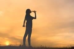 妇女饮用水的剪影 库存照片