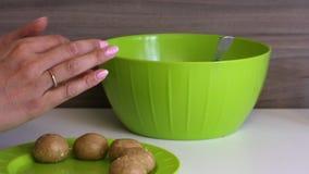 一个女人手里拿着浓缩牛奶卷饼 准备球在板子上 蛋糕棒的烹饪基础 股票录像