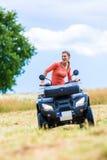 妇女驾驶越野与方形字体自行车 库存照片