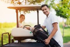 妇女驾驶高尔夫球汽车 前景的一个人在树干旁边站立并且拔出高尔夫俱乐部 库存照片