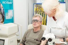 妇女验光师检查一个人的视觉 免版税库存照片