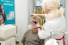 妇女验光师检查一个人的视觉 库存照片