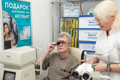 妇女验光师检查一个人的视觉 免版税库存图片