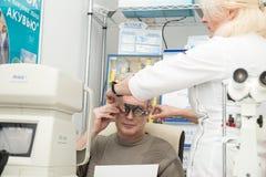 妇女验光师检查一个成熟人的视觉 免版税库存图片