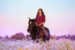 妇女骑乘马在日落的用花装饰的草甸 图库摄影