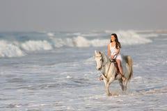 妇女骑乘马海滩 库存图片