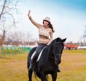 妇女骑乘马,米黄套头衫,牛仔裤,帽子,关闭 库存照片