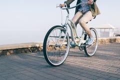 妇女骑沿海的一辆美丽的自行车 免版税库存照片
