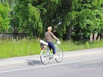 妇女骑自行车在高速公路一边反对绿色树背景在一个晴朗,晴天 ty供选择的Masow 图库摄影