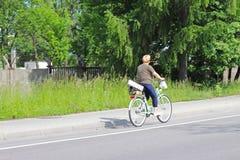 妇女骑自行车在高速公路一边反对绿色树背景在一个晴朗,晴天 ty供选择的Masow 免版税库存图片