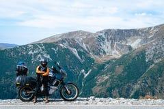 妇女骑自行车的人和adveture摩托车顶面山路 旅行,假期在欧洲,摩托车骑士方式,旅游业,Transalpina,罗马尼亚 库存照片