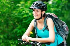 妇女骑自行车的人拿着一朵黄色花 图库摄影