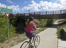 妇女骑自行车者乘坐圣塔菲河足迹 库存照片