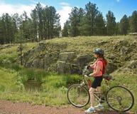 妇女骑自行车者在森林足迹停留 库存图片