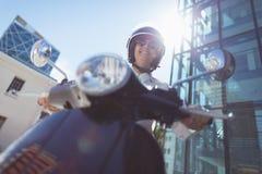 妇女骑马小型摩托车低角度视图  免版税库存图片