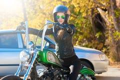 妇女骑马摩托车 黑夹克,盔甲 关闭 免版税库存照片