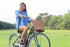 妇女骑马自行车在公园,室外 库存图片