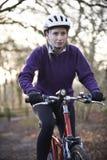妇女骑马登山车通过森林地 免版税库存照片