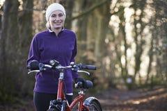 妇女骑马登山车通过森林地 库存图片