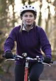 妇女骑马登山车通过森林地 免版税图库摄影