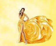 妇女黄色礼服,在典雅的长的褂子的愉快的时装模特儿 免版税库存照片