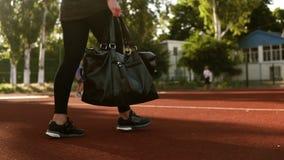 妇女黑绑腿的和有黑体育袋子的由在体育场的轨道线在手中去 体育袋子-瞄准的英尺长度 股票视频