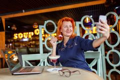 妇女,在咖啡馆在智能手机坐,吃点心并且做selfie 库存照片
