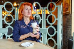 妇女,在咖啡馆坐并且拿着与一份芬芳咖啡饮料的一块玻璃 库存图片