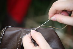妇女,当缝合在皮革时的一件礼服 库存照片