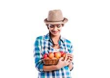 妇女,拿着篮子用苹果的被检查的衬衣 秋天收获 免版税库存图片