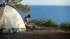 妇女,露营车,在帐篷旁边烹调食物在陡峭的海岸线边缘在一个杉木树丛里有一个宏伟的视图 免版税库存照片