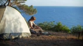 妇女,露营车,在帐篷旁边烹调食物在陡峭的海岸线边缘在一个杉木树丛里有一个宏伟的视图 库存图片
