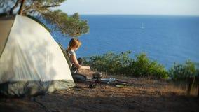 妇女,露营车,在帐篷旁边烹调食物在陡峭的海岸线边缘在一个杉木树丛里有一个宏伟的视图 免版税库存图片