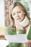 妇女读书信件在受到脖子伤以后 免版税库存图片