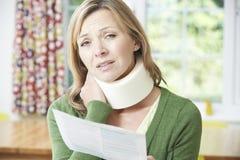妇女读书信件在受到脖子伤以后 免版税库存照片
