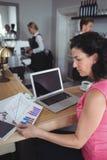 妇女读书图表图和工作与膝上型计算机在酒吧柜台 库存照片
