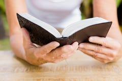 妇女读书圣经的中央部位 免版税图库摄影