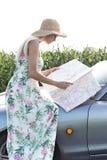 妇女读书地图侧视图,当坐敞篷车时 免版税库存照片