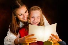 妇女读书对年轻人的圣诞卡 库存图片