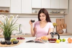 妇女读书杂志和饮用的茶在厨房里 免版税库存图片