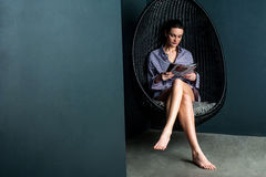 妇女读书杂志,在摇摆的椅子的开会 免版税库存照片