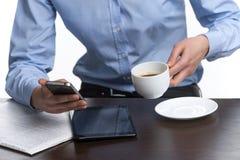 妇女读书特写镜头从电话的,当喝咖啡时 免版税库存照片