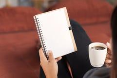 妇女读书笔记本和藏品咖啡杯 库存图片